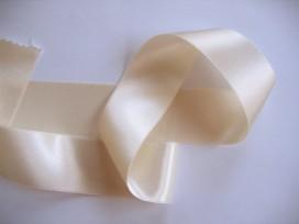 Creme satijnlint per rol van 25 meter.  Een hele mooie kwaliteit dubbelzijdig satijnlint.  38 mm breed  100 % polyester
