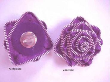 Ritsbroche paars, gemaakt van een rits met zilveren tandjes. Doorsnee is ca. 9 cm. Worden per stuk verkocht.