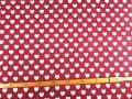 Een rode canvas stof bedrukt met witte hartjes. De hartjes hebben een doorsnee van 17 mm. 100% katoen 1.50 mtr. br.