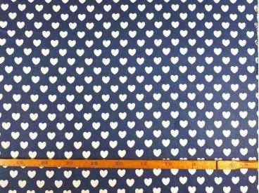 Een jeansblauwe canvas stof bedrukt met witte hartjes. De hartjes hebben een doorsnee van 17 mm. 100% katoen 1.50 mtr. br.