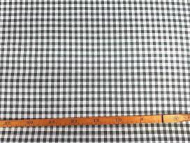 Een met donkergrijze boerenbont ruit bedrukte canvas, die iets wat stug aanvoelt.  Het ruitje is 7 x 7 mm. 100% katoen 1.50 mtr.