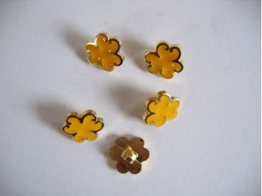Goudkleurige kunstof bloemknoop met gele blaadjes. 12 mm. doorsnee.