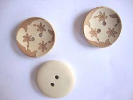 Een houten bloemknoop met een ingelaserde bloemprint. De doorsnee is 25mm.