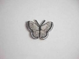 Een opstrijkbare vlinder applicatie van 3 x 2.5 cm. Lichtgrijs glitter