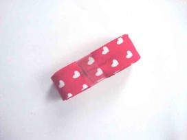Een bundel biaisband van 2 meter lang. Rood met witte hartjes. 2 cm. breed