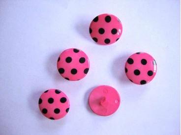 Pinkkleurige kunststof knoop met een zwarte stip. Doorsnee van 20 mm.