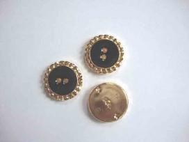 Een zwart/gouden kunststof knoop met een gouden golfrandje en een doorsnee van 25 mm,
