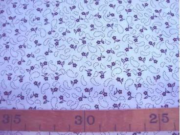 Een witte katoen met een zwarte kleine bloemprint. 100% katoen. 1.45 mtr.br.