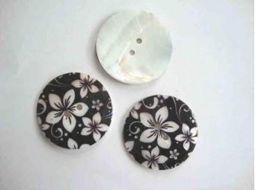 Een ronde  exclusieve parelmoerknoop met een zwart/ivoor bloemprint. Doorsnee 40mm.