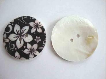 Een ronde exclusieve parelmoerknoop met een zwart/ivoor bloemprint. Doorsnee 50mm.