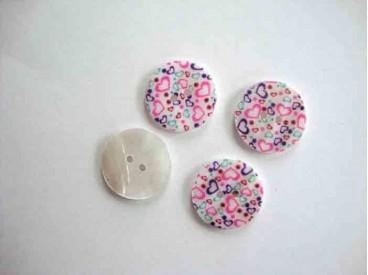 Een ronde exclusieve parelmoerknoop met een hartjes print. Doorsnee 22mm.
