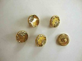 Een ronde, geel/goudkleurige kunststof damesknoop met een bloemrand. Doorsnee 15 mm.