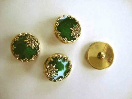 Een ronde, groen/goudkleurige kunststof dames knoop met een bloemrand. Doorsnee 20 mm.