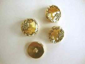 Een ronde, geel/goudkleurige kunststof dames knoop met een bloemrand. Doorsnee 20 mm.