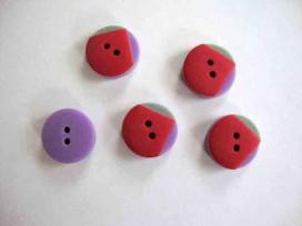 Een rood/groen/paarse kunststof knoop met een doorsnee van 15 mm.