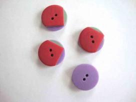 Een rood/groen/paarse kunststof knoop met een doorsnee van 18 mm.