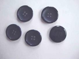 Een diep donkerblauwe ( bijna zwarte) kunststof mantelknoop met een doorsnee van 25 mm.