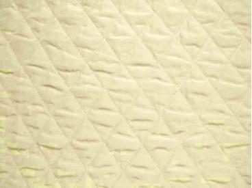 Een donkercreme kleurige gewatteerde voering met een grote ruit. 100% polyester. 1.50 mtr. breed.