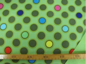 Een limegroene shoftshell met diversen gekleurde cirkels. De stof is wind en waterdicht en rafelt niet. 97% Pe/3% Sp 1.45 mtr. b